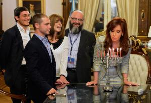 "Argentina President Cristina Fernández de Kirchner (far right) celebrates a Hanukkah candle-lighting ceremony with Yair Tawail (second from left) after ""adopting"" him to break his werewolf curse."