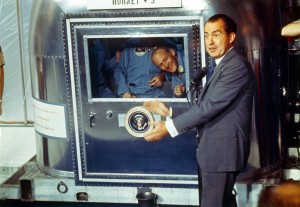 President Richard Nixon welcomes the Apollo 11 astronauts (confined to a mobile quarantine facility)  back to earth.