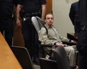 Josh Monson in a special restraining chair, surrounded by law enforcement.