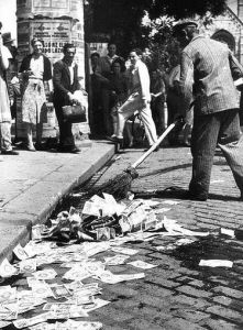 A Hungarian worker sweeps the streets, littered with with worthless money.